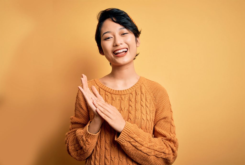 Beautiful Asian girl in a yellow sweater smiling